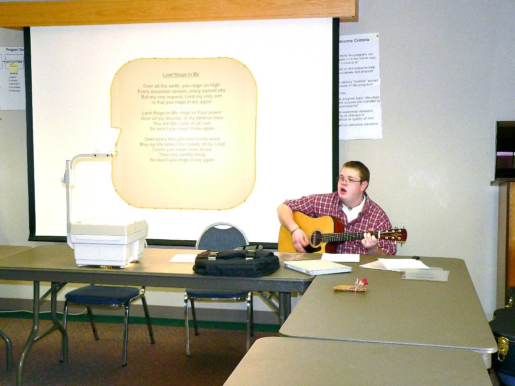 Tom with guitar leads participants in praise and worship