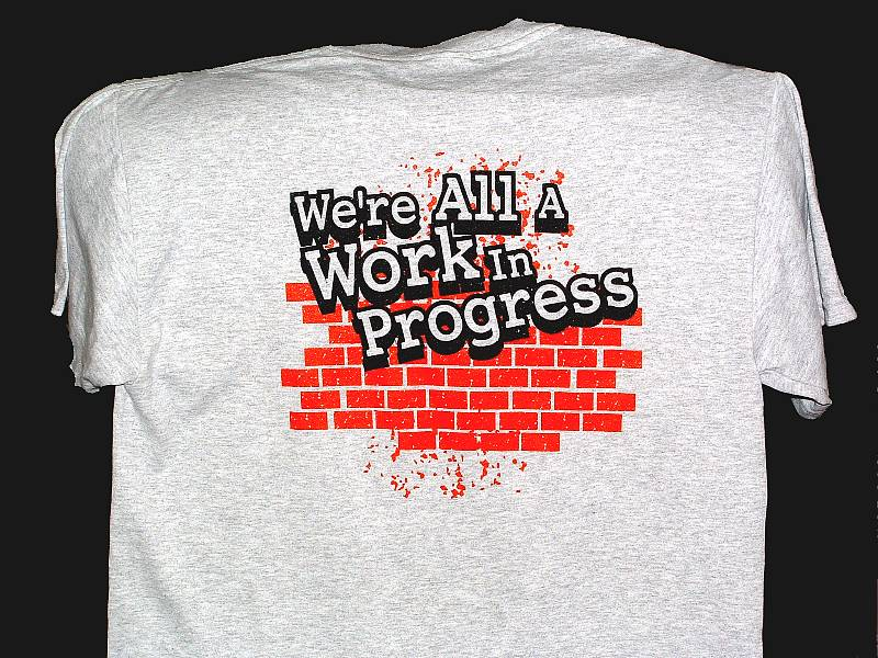 Back view of t-shirt. An incomplete brick wall, bright red, phrase 'We Are All A Work In Progress'